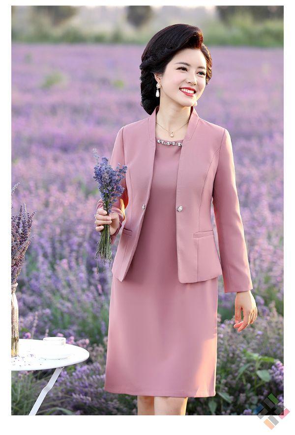 Người phụ nữ đang mặc chiếc đầm suông màu hồng và cầm một bó hoa màu tím