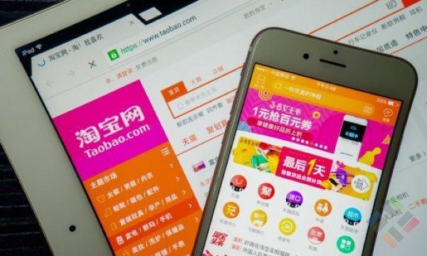 Một màn hình điện thoại và màn hính máy tính đang hiển thị trang chủ của Taobao